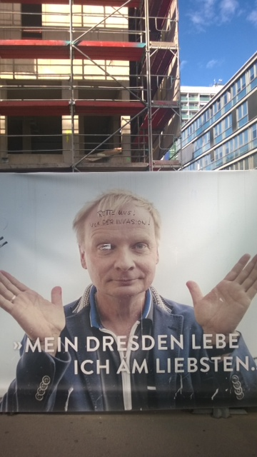 "Advertising on the construction site of an apartment building across the street from Dresden Central Station. The sign promotes the great location of the apartments. On the man's forehead, someone scribbled ""Save us! From the Invasion!"" likely referring to the arriving refugees. Photo by the author (2015)."